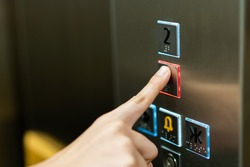 People pressing the button in the lift and select the first floor by using the forefinger. Elevator control panel in small building close up. Bell alphabet on the button in the passenger lift.