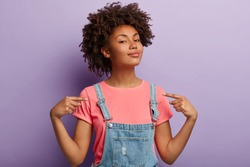People, pride, arrogance concept. Self assured proud woman has Afro hairstyle satisfied with own high achievements, feels confident, keeps head raised, being like hero, isolated on purple wall