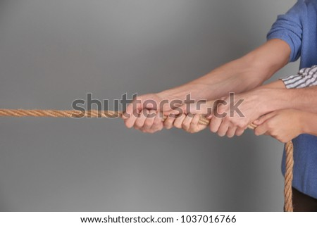 People pulling rope together on grey background. Unity concept #1037016766