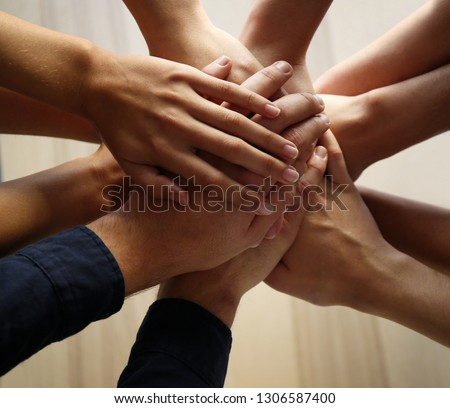 People putting hands together, closeup. Unity concept