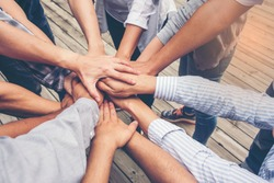 People putting their hands together. Friends with stack of hands showing unity and teamwork.