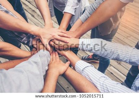 People putting their hands together. Friends with stack of hands showing unity and teamwork. #1052015711