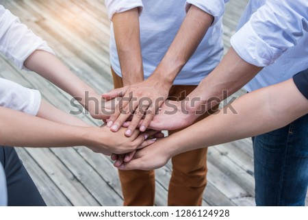 People putting their hands together. Friends with stack of hands showing unity and teamwork.  #1286124928