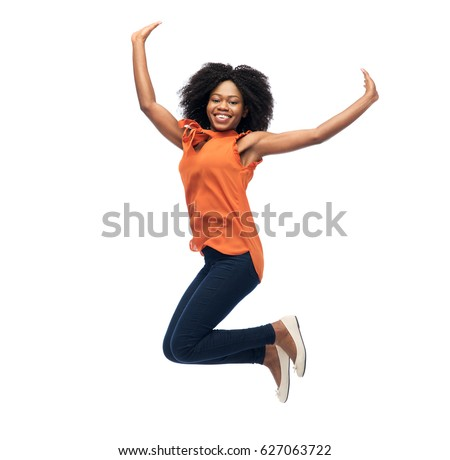 people, race, ethnicity and motion concept - happy african american young woman jumping over white