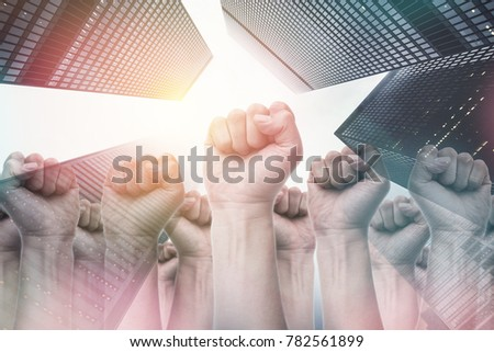 people raise fist air fighting for their rights with sun effect on building backgrounds, labor movement, election movement, strike movement #782561899