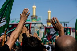 People raise their hands to the sky between the shrine of Abbas ibn Ali and Imam Hussein in Karbala, Iraq