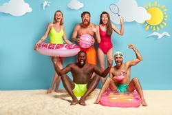 People, recreation and summer concept. Overjoyed mixed race friends clench fists, have fun and play on hot beach, swim with inflated rings, have friendly relationship, play tennis, football.