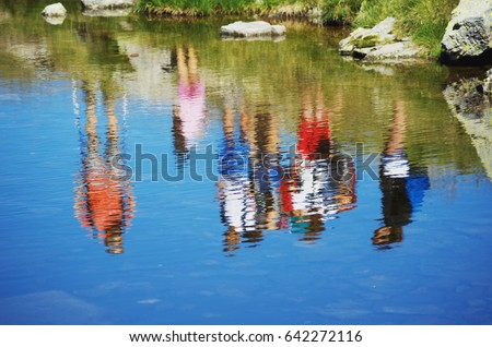 People reflected in the water. Hikers reflected in the surface of alpine lake.