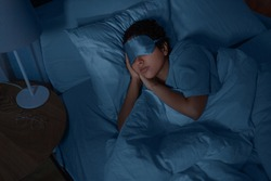 people, relax and comfort concept - young african american woman in eye mask sleeping in bed at home at night