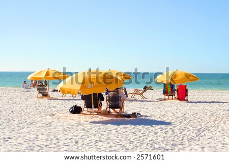 people relaxing on beach chairs under umbrellas in Clearwater Beach, Florida, USA