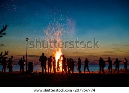 Shutterstock People resting near big bonfire outdoor at night