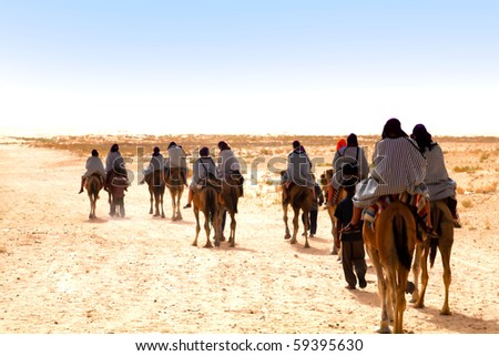 People ridding by camels on the Sahara desert