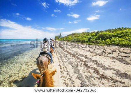 People riding on horse back at the Caribbean beach. Grand Cayman.