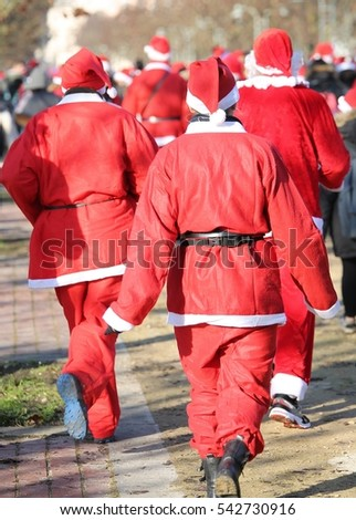 people run during the sporting event called Running with Santa Claus in the public park of the city at Christmas