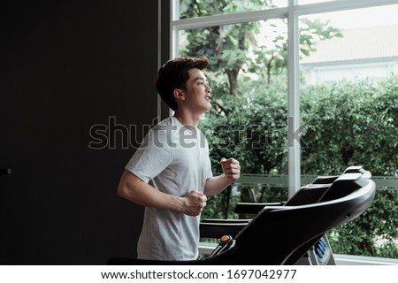 People running in machine treadmill at fitness gym. young man running on a treadmill at home. Male athlete workout on running exercise machine.