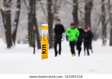 People running in park on snowy winter. Man runner jogging white snow in cold weather nature in forest.