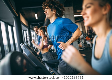 People running on a treadmill in health club
