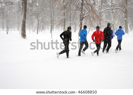 People running on snow in winter park, runners exercising outdoors, motion blur.