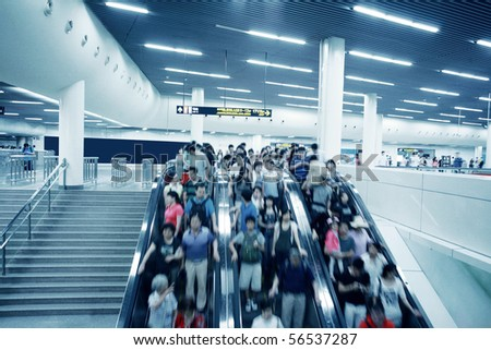 People rush on a escalator motion blurred