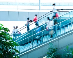 People rush on escalator motion blurred.