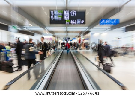 People rushing in airport gate seen from escalator