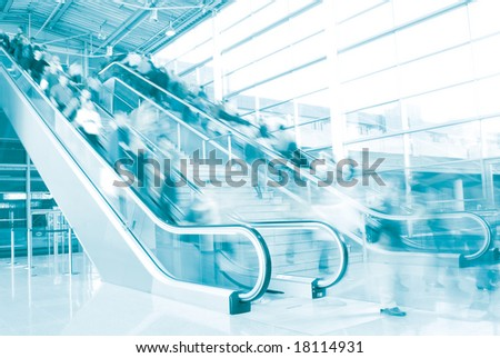 People rushing on escalator in business center, mall or airport to work with motion blur in blue tone