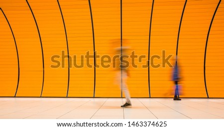 People rushing through a subway corridor (motion blur technique is used to convey movement) #1463374625
