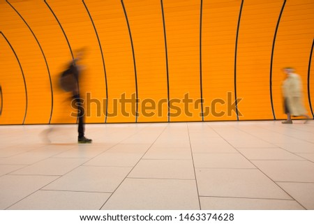People rushing through a subway corridor (motion blur technique is used to convey movement) #1463374628