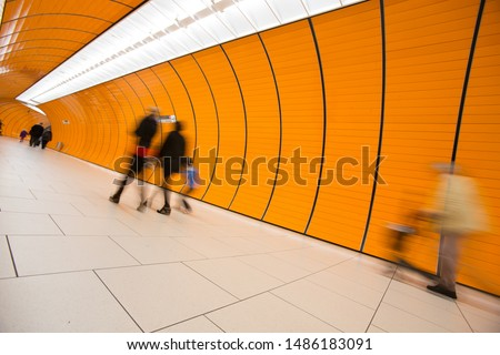 People rushing through a subway corridor (motion blur technique is used to convey movement) #1486183091