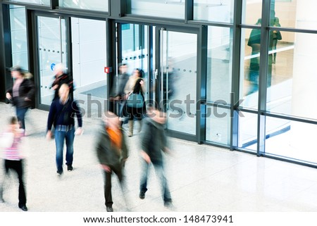 people rushing through corridor