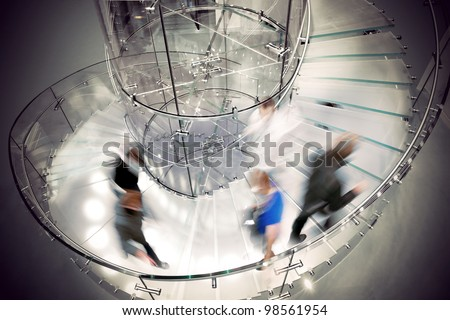 People rushing up and down modern transparent spiral staircase