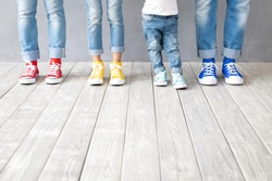 People's feet in colorful sneakers. Happy family - father, mother, son and daughter indoor. Parents and children at home