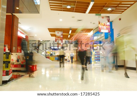 people's motion blur in busy shopping mall
