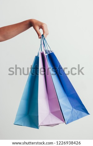 people, sale, consumerism, advertisement and black friday concept - close up of hand holding shopping bags