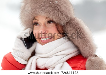 people, season and leisure concept - happy smiling woman in winter fur hat calling on smartphone outdoors #726811192