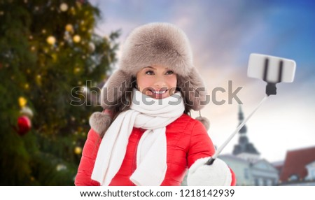 people, season and leisure concept - happy smiling woman in winter fur hat taking selfie by smartphone over christmas tree at tallinn old town hall square background