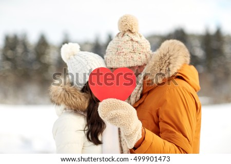 people, season, love, christmas and valentines day concept - happy couple hiding faces behind blank red heart over winter landscape