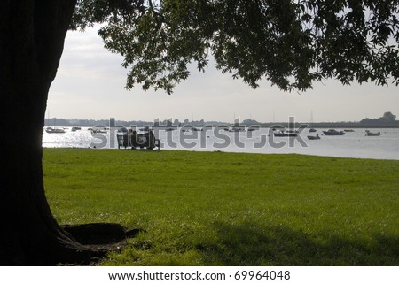 People seated on bench at Bosham in Chichester Harbour. West Sussex. England