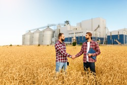 People shaking hands in a wheat field, farmer's agreement. Grain elevator terminal on background. Agriculture agronomist business contract concept