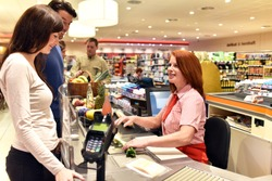 people shopping at the supermarket - paying at the checkout with a friendly cashier