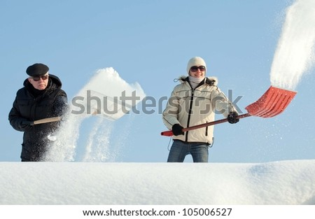 People shovelling snow on a roof against blue sky
