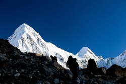People silhouette hiking in mountains. Hikers in Himalaya Mountains over Pumo ri snow high peak