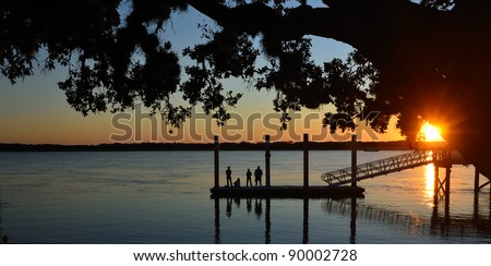 people silhouetted at sunset on fishing dock florida usa
