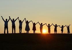 People silhouettes on sunset meadow having fun
