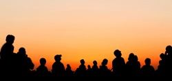 People silhouettes watching sunset sky during airshow