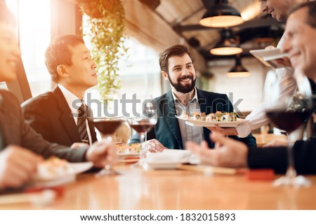 People sit at a table eating sushi and drinking wine. The waiter brings sushi to business people who stipulate business ideas in a restaurant.