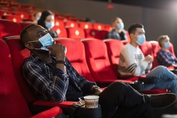 People sit in the cinema hall and watch a movie wearing medical masks and keep their distance. Covid-19 and the film industry