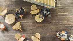 people sit on the chairs and table on the pattern wood floor and direct light on the empty ground (top aerial view)