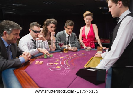 People sitting at table playing poker in a casino