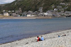 People sitting on a shingle beach  enjoying the view of Barmouth  across the mouth of the Mawddach river in Gwynedd, Wales, UK.